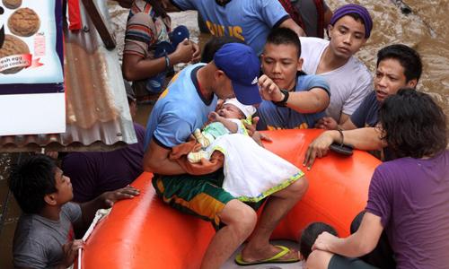 Cảnh sát sơ tán một em bé ở thành phố Cagayan ngày 22/12. Ảnh: AFP.