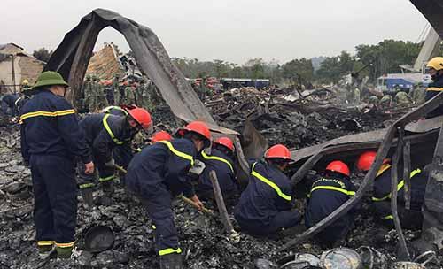 Cảnh sát cứu hoả xới từng lớp xỉ than tìm thi thể nạn nhân. Ảnh: Lam Sơn.