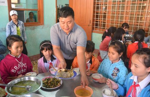 Đến bữa ăn, thầy Điệp xuống kiểm tra thức ăn của học sinh bán trú. Ảnh:Đắc Thành.