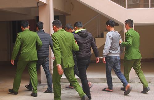 Bốn bị cáo được cảnh sát dẫn giải tại sân tòa. Ảnh: Đức Hùng