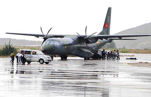 Nhóm khủng bố khống chế con tin đưa ra khỏi máy bay, chuyển lên ôtô. Ảnh: Quốc Thành