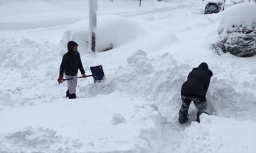 Người dân dọn tuyết trước cửa nhà ở Erie. Ảnh: Reuters.
