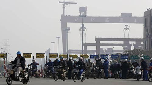 Công nhân một khu công nghiệp nặng ở thành phố Nam Thông, tỉnh Giang Tô sử dụng xe điện và xe máy để về nhà sau khi tan ca. Ảnh: Reuters.