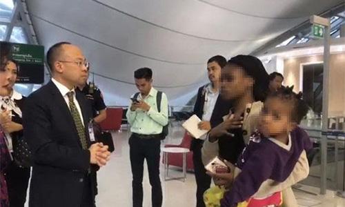 Phó giám đốc sân baySuvarnabhumi (trái) hôm 26/12nói chuyện với một phụ nữ trong gia đìnhZimbabwean đang mắc kẹt tại sân bay này từ cuối tháng 10. Ảnh: Nation.