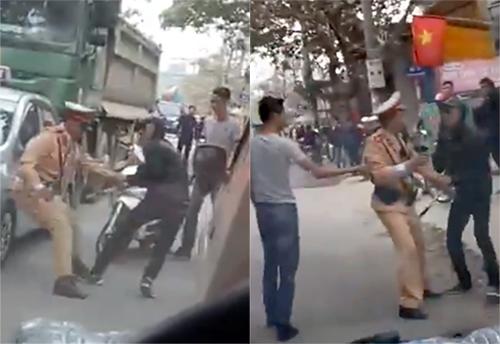 Hai thanh niên giằng co, kéo đẩy cảnh sát giao thông vào lề đường để cho xe tải chạy thoát. Ảnh chụp từ clip