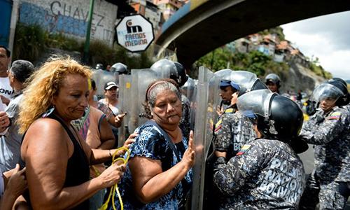 Người biểu tình đụng độ với cảnh sát ở Caracas. Ảnh: AFP.