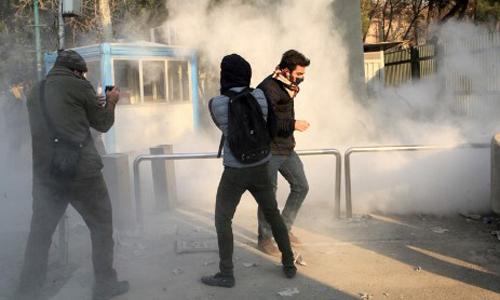 Sinh viên Iran tránh khí hơi cay tại Đại học Tehran trong cuộc biểu tình ở Tehran ngày 30/12. Ảnh: AFP.