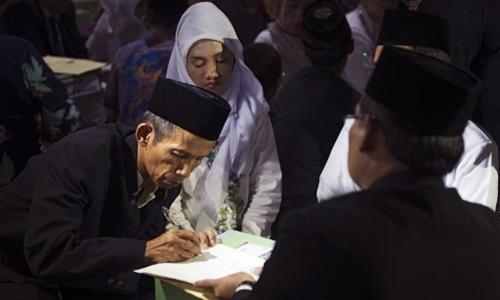 Một chú rể lớn tuổi ký giấy chứng nhận kết hôn. Ảnh: AFP.