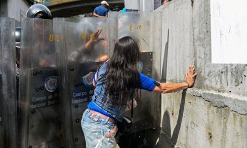 Một phụ nữ đụng độ với cảnh sát chống bạo động trong cuộc biểu tình chống tình trạng thiếu thực phẩm ở Caracas ngày 28/12. Ảnh: AFP.