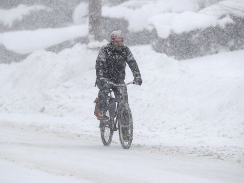 [Caption]A man rides on his bicycle as fresh snow falls on Dec. 29, 2017, in Erie, Pa. Tony Dejak, AP