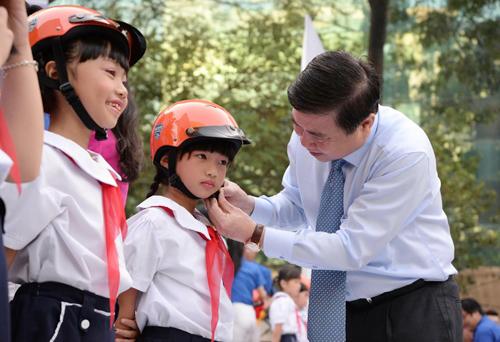 Chủ tịch UBND TP HCM Nguyễn Thành Phong đội mũ bảo hiểm cho các em học sinh tại buổi lễ. Ảnh: Hữu Nguyên
