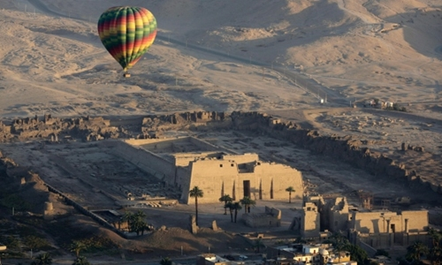 A hot air balloon flies over the mortuary temple of Ramsis III at Medinet Habu on the west bank of the Nile River in Luxor, Egypt, in 2016. Egyptian officials say a sightseeing balloon carrying foreign tourists over the southern city of Luxor crash landed Friday. (Amr Nabil/Associated Press)