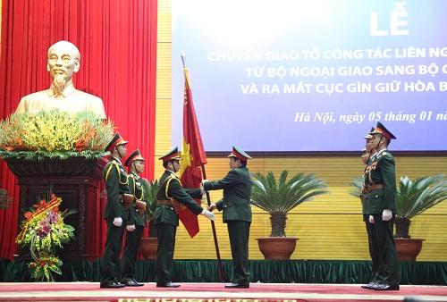Đại tướng Ngô Xuân Lịch, Bộ trưởng Bộ quốc phòng trao Quân kỳ Quyết thắng cho Cục Gìn giữ hòa bình Việt Nam. Ảnh: Thanh Tùng