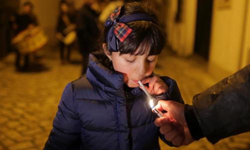 Một người lớn châm lửa cho bé gái hút thuốc. Ảnh: AP.