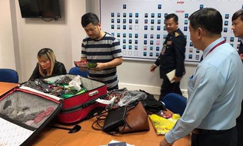 Giới chức Campuchia khám xét vali chứa heroin của Ve Thi Tran. Ảnh: Tổng cục Di trú Campuchia