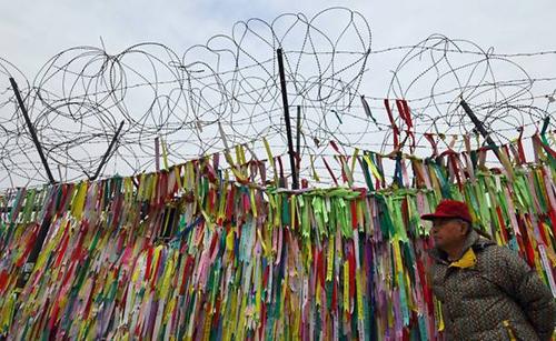 Một khách du lịch đi ngang qua hàng rào dây thép gai, tại khu vực phi quân sự liên Triều, cài những chiếc ruy-băng cầu chúc hai miền Triều Tiên thống nhất và hòa bình. Ảnh: AFP.
