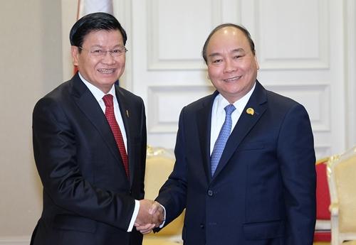Thủ tướng Nguyễn Xuân Phúc gặpThủ tướng Lào Thongloun Sisoulithn tại Campuchia ngày 10/1. Ảnh: VGP.
