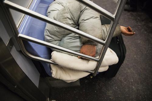 Một người vô gia cư ngủ trên tuyến tàu điện ngầm E. Tuyến tàuchạy suốt 50 phút dưới lòng đấtnày trở thành nơi trú ngụ thường xuyên của những người không nhà không cửa ở thành phố New York, Mỹ. Ảnh:New York Times.
