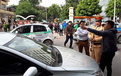 Sáng 11/1, tại phố Phủ Doãn, Hoàn Kiếm, Hà Nội cảnh sát giao thông dừng nhiều xe Uber, Grab đi vào đường cấm để nhắc nhở. Ảnh: Phương Sơn