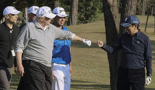 Tổng thống Donald Trump (trái) đập tay với Thủ tướng Shinzo Abe trong một trận golf. Ảnh: AFP.