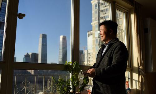 ông Zou Yi bên khung cửa sổ ở Bắc Kinh, Trung Quốc. Ảnh: AFP.