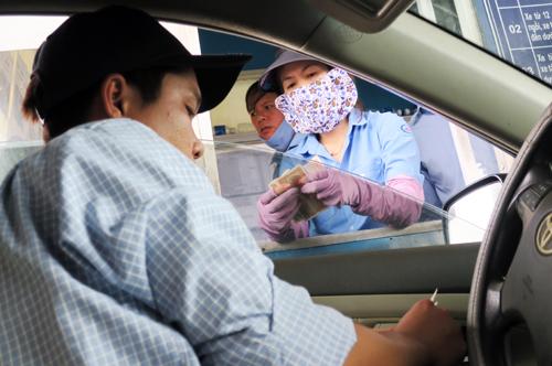 Tài xế dùng tiền lẻ mua vé qua trạm BOT Sông Phan. Ảnh: Tư Huynh.