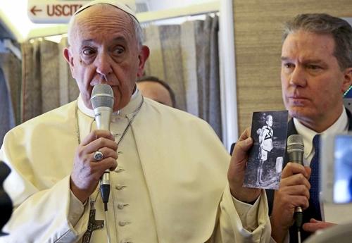 Giáo hoàng Francis cho các phóng viên xem ảnh chụp các nạn nhân của bom nguyên tử ở Hiroshima, Nhật Bản, khi trả lời báo giới ngày 15/1. Ảnh: AFP.