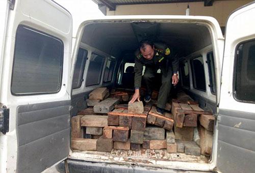 Cảnh sát niêm phong số gỗ lậu trên xe khách 16 chỗ. Ảnh: Đ.H
