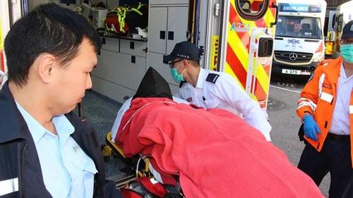 Người đàn ông Hàn Quốc nghi sát hại vợ con được chuyển lên xe để đưa đến bệnh viện. Ảnh: AFP/Apple Daily.