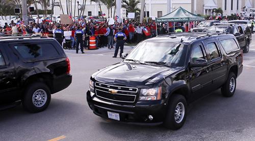 Đoàn xe chở gia đình tổng thống đi qua nhóm người biểu tình để ra sân bay. Ảnh: Palm Beach Post