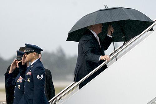 Tổng thống Trump cầm ô lên máy bay trước vợ con. Ảnh: AP