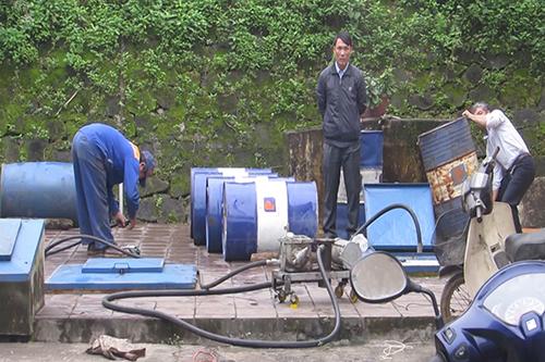 Nhân viên công ty xăng dầu Quảng Trị kiểm tra bồn xăng tại cửa hàng phát hiện bán xăng pha nước. Ảnh: H.Th