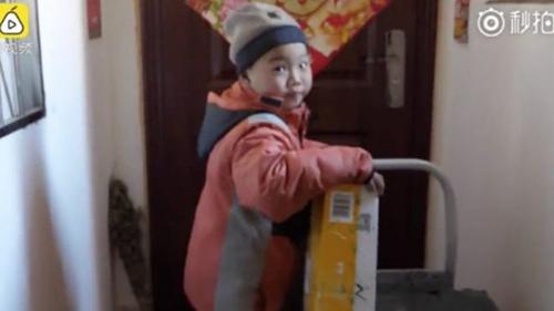 Cậu bé Tiểu Li vận chuyển các thùng hàng ở thành phố phía đông Thanh Đảo.