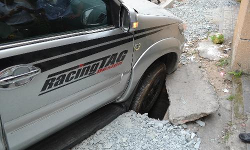 Bánh trước của ôtô nằm trọn trong hố ga công trình. Ảnh: Thảo Dân
