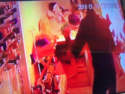 Camera ghi lại hình ảnh người đàn ông xách can chất lỏng đi vào cửa hàng.