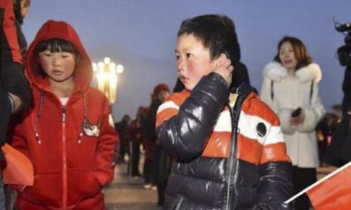 Cậu bé tóc băng Vương Phú Mãn và chị gái đi xem lễ thượng cờ ở quảng trường Thiên An Môn. Ảnh: Baijiahao.baidu.com.