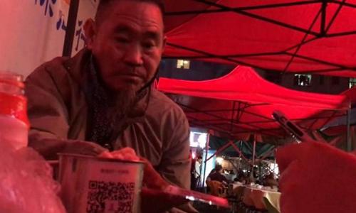 Một người ở quán nhậu vỉa hè tại Thâm Quyến cho tiền ông Vương qua chiếc cốc in mã QR. Ảnh: Hk01.