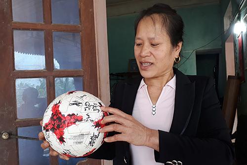 Bà Nguyệt mang quả bóng có chữ ký của đội U23 cho dân làng xem. Ảnh: Lam Sơn.