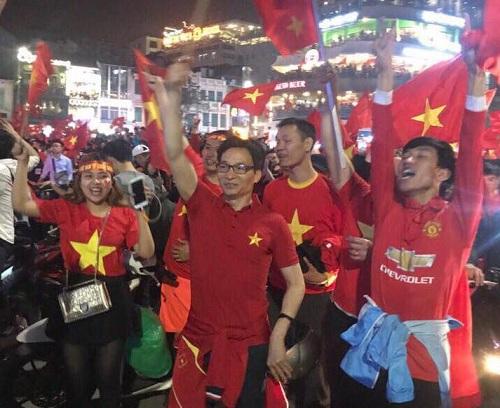 Phó thủ tướng Vũ Đức Đam vẫy cao lá cờ, chung vui cùng cổ động viên Hà Nội.
