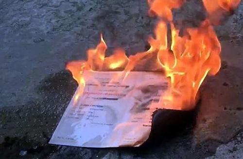 Tấm bằng tốt nghiệp đại học bị đốt . Ảnh cắt từ clip.