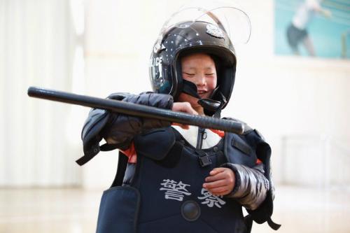 Vương Phú Mãn được cho mặc thử quần áo của cảnh sát chống bạo động. Ảnh:Visual China Group