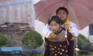 Vượt mưa gió, bé gái Trung Quốc cõng anh trai 12 tuổi đi học