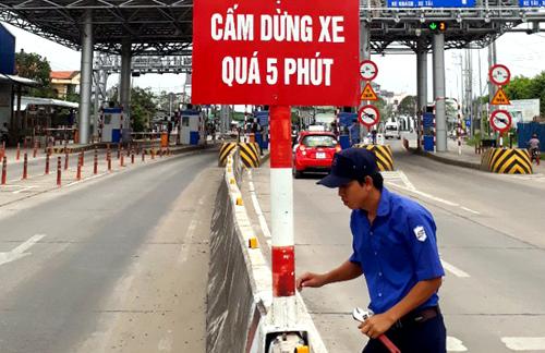 Nhân viên trạm BOT T2 trên quốc lộ 91 lắp đặt biển cấm dừng xe quá 5 phút. Ảnh: Cửu Long.