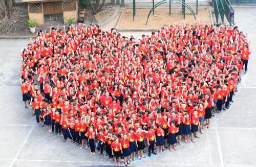 Thầy cô và học sinh trường Tiểu học Nguyễn Văn Trỗi xếp hình trái tim. Ảnh: Tiểu học Nguyễn Văn Trỗi.
