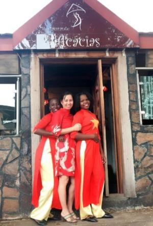 Chị Hương và hai nhân viên mặc áo dài hìnhcờ đỏ sao vàng trước nhà hàngAcacias. Ảnh: NVCC