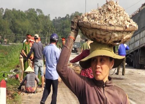 Người dân Quảng Ngãi giúp cảnh sát giao thông dọn dẹp củ mì đổ văngxuốngđường tránh quốc lộ. Ảnh: Thạch Thảo.