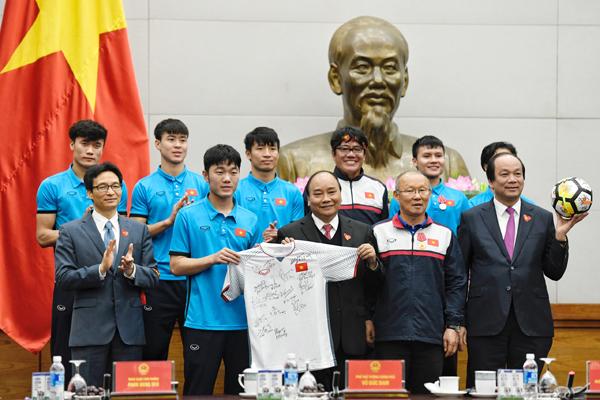 Đội trưởng Lương Xuân Trường trao quà tặng của Đội tuyển U23 cho Thủ tướng. Ảnh: Giang Huy
