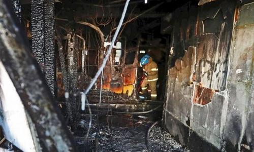 Cảnh sát khám nghiệm hiện trường vụ cháy. Ảnh: AFP.