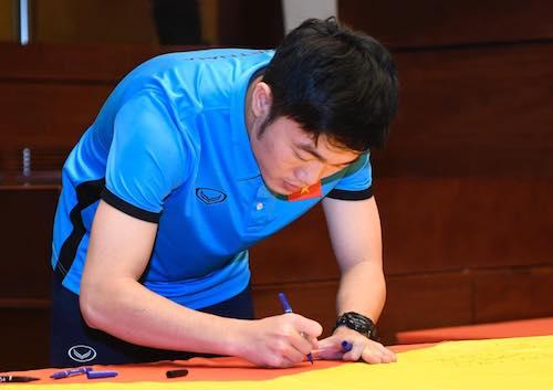 Đội trưởng U23 Xuân Trường ký vào lá cờ Tổ quốc 54 m, đại diện cho 54 dân tộc. Ảnh: Giang Huy