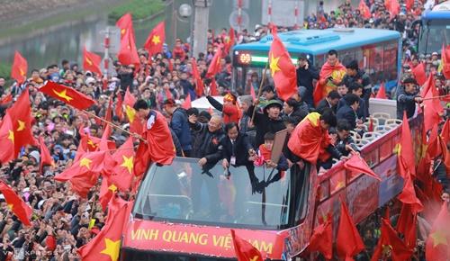 Chiếc xe buýt chở đội diễu hành qua các tuyến đường ngập cờ đỏ sao vàng ngày 28/1. Ảnh:Đỗ Mạnh Cường.
